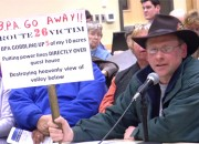 Jason Carpenter holds a sign protesting the fact that a proposed BPA line would impact his rural property.